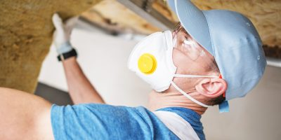 Insulating Material Installation by Caucasian Contractor Worker. Building Insulation.