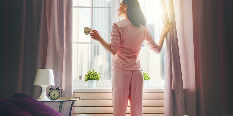 Happy young woman enjoying sunny morning and coffee. Girl drinks cup of tea, hot beverage near window.